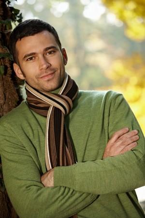 shawl: Outdoors portret van happy jonge man die in de herfst park op boom. Stockfoto