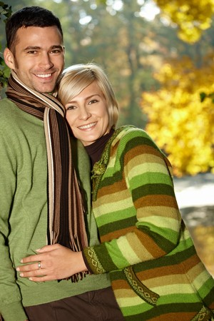 30s: Portrait of happy young love couple in autumn park looking at camera, smiling.