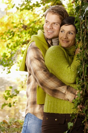 Portrait of happy young couple in autumn park standing at tree, smiling. photo