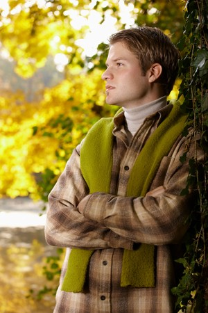 fantasize: Outdoors portrait of happy young man standing in autumn park at tree, thinking. Stock Photo