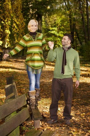 Happy couple walking in autumn park, woman balancing on bench. photo