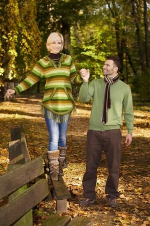 balancing: Happy couple walking in autumn park, woman balancing on bench.