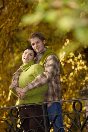 Happy couple standing embracing in autumn park, smiling. photo