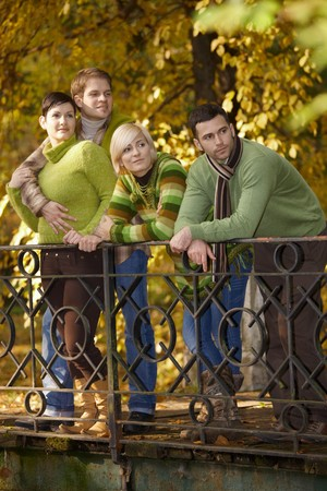 Two smiling couples standing in autumn park, leaning to railing. photo