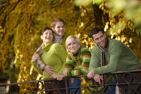 Happy young people standing in autumn park, leaning to railing. photo