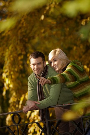 Outdoors portrait of happy couple standing in autumn park, woman showing something to man, smiling. photo