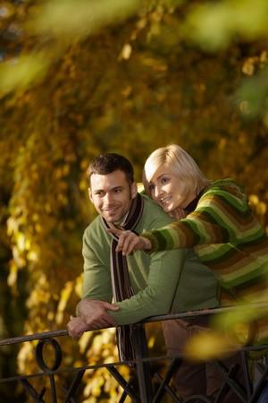 amigos abrazandose: Retrato de al aire libre de la feliz pareja permanente en oto�o de Parque, mujer mostrando algo al hombre, sonriendo.