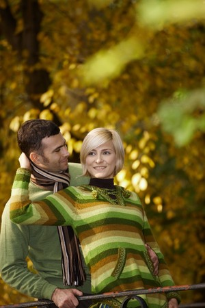 Portrait of happy young couple embracing in autumn park, smiling.