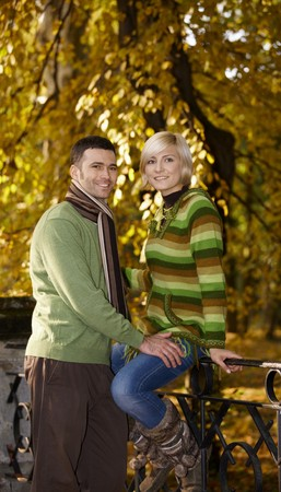 Loving couple on autumn walk in park. Woman sitting on railing, looking at camera, smiling. photo