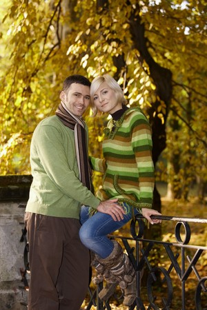 Portrait of happy couple in autumn park. Woman sitting on railing, leaning to each other, smiling. photo