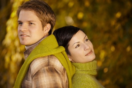 falling in love: Content couple standing back to back in park, daydreaming in autumn. Stock Photo