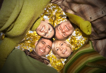 Group of happy friends standing with their heads together in autumn forest, smiling. Low angle view. photo