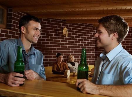 horizontal bar: Smiling young men sitting at bar in pub drinking beer, women sitting in background. Stock Photo