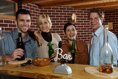 Happy young people standing at bar in pub, drinking beer, looking at camera, smiling. photo