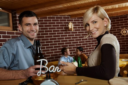 Portrait of young couple in bar, drinking beer, smiling at camera, friends in background. photo