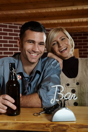 Portrait of happy young couple in pub, laughing at camera, drinking beer. photo