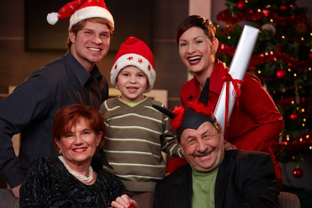 Portrait of happy family at christmas eve. Father and son wearing Santa Claus hat, smiling. Stock Photo - 7791823