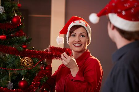 Happy young woman decorating christmas tree,  looking at man, smiling. photo
