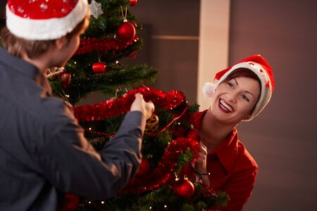 Happy young couple wearing santa claus hat, decorating christmas tree,  laughing to each other. photo