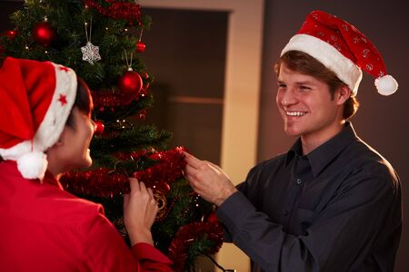 Happy young couple wearing santa claus hat, decorating christmas tree,  smiling to each other. photo