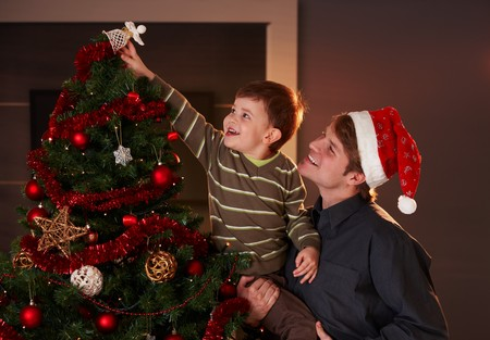 putting up: Dad helping son to decorate christmas tree, boy putting up the top ornament, smiling.