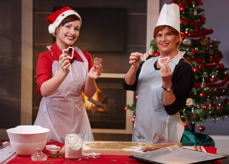 Mother and daughter presenting christmas cookies and form at baking for the holiday. photo