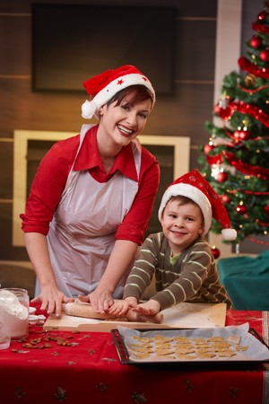 Happy mum baking with son for christmas, looking at camera, smiling. photo