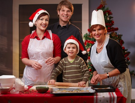 Portrait of happy family of parents, small son and grandmother baking christmas cake together. photo