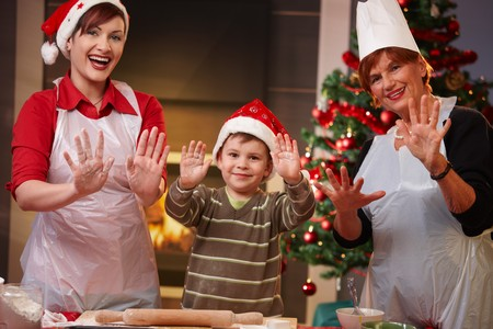 Portrait of happy child with mom and grandmother at christmas baking, raising doughy hands, smiling. photo