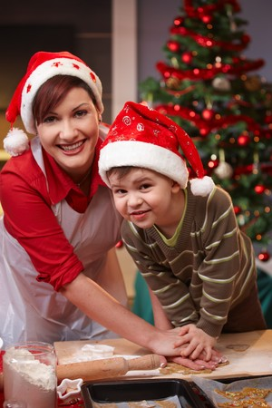Mum and son having fun at christmas baking, looking at camera, smiling. photo
