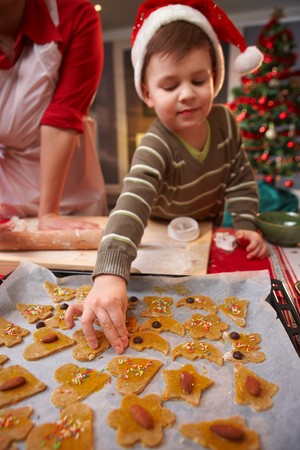 Small child in santa claus hat helping with christmas cake. photo