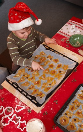 Small boy sitting at table pointing at christmas cake in baking pan. photo