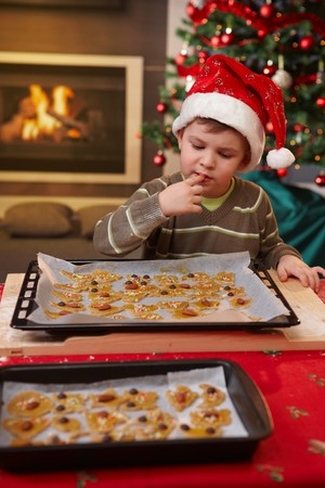 Young boy in santa claus hat tasting christmas cake at table. photo