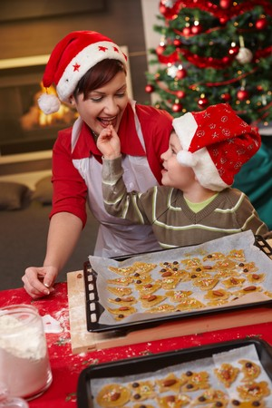 Smiling mum and small son tasting christmas cake together at table. photo