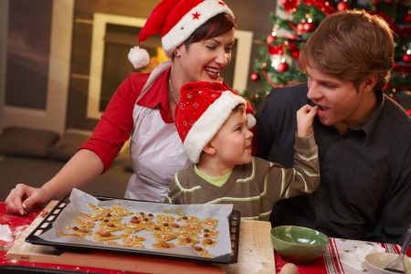 Small son helping dad tasting christmas cake at table, mother watching, laughing. Stock Photo - 7791817