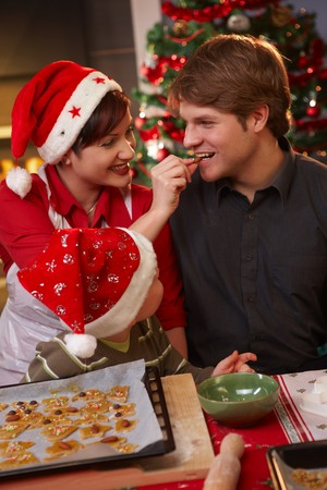 Smiling wife handing christmas cake to father to taste, kid watching. Stock Photo - 7791781