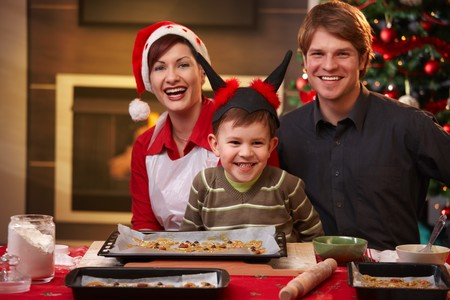 Christmas portrait of happy family of three, looking at camera, smiling. photo
