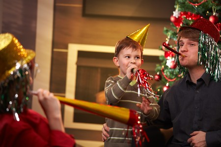 new age: Happy family celebrating new years eve together, wearing funny hat and blowing horn.