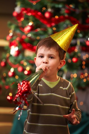 new ages: Little boy in new years eve hat blowing horn, looking at camera.