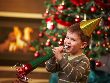 new age: Little boy laughing on new years eve, wearing shiny hat and blowing horn, looking at camera, christmas tree in background.