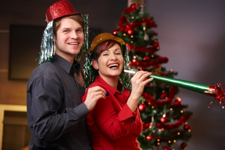 new year eve: Portrait of happy couple in funny hat blowing horn on new year eve with christmas tree in background.