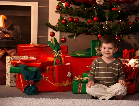 only boys: Portrait of little boy sitting on floor in front of Christmas tree and presents, smiling. Stock Photo