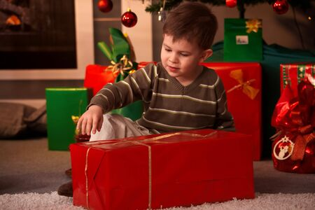 Happy little boy sitting on floor wrapping out christmas present in front of christmas tree and fireplace. photo