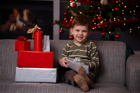 Portrait of happy little boy sitting on couch with christmas presents, smiling. Stock Photo - 7792006
