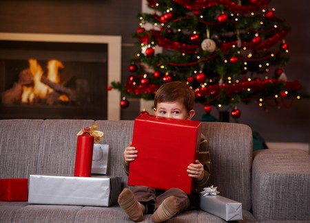 Little boy sitting on couch hiding behind gift box, looking over it. Stock Photo - 7791995