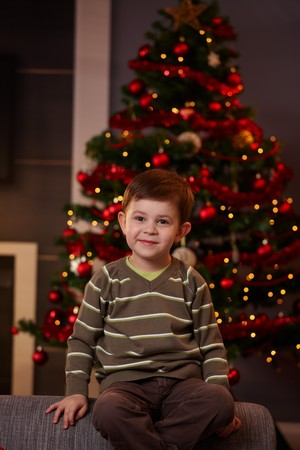 Portrait of little boy sitting in front of christmas tree, smiling. photo