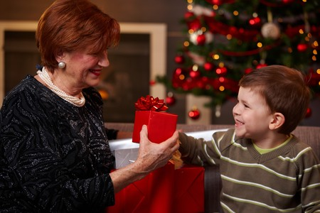 Grandson giving christmas present to happy grandmother, smiling.   photo