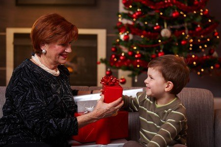 Little boy giving christmas present at christmas, smiling.   photo