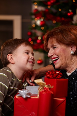 Portrait of happy grandmother and grandson looking to each other over christmas presents, smiling.         photo