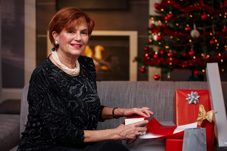 Senior woman sitting on couch at home, wrapping christmas presents, smiling. Stock Photo - 7791989